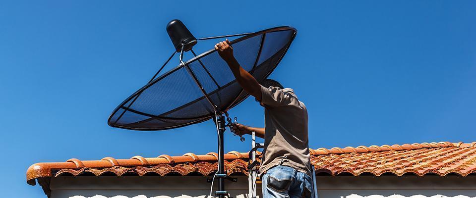mężczyzna ustawia antenę telewizyjną